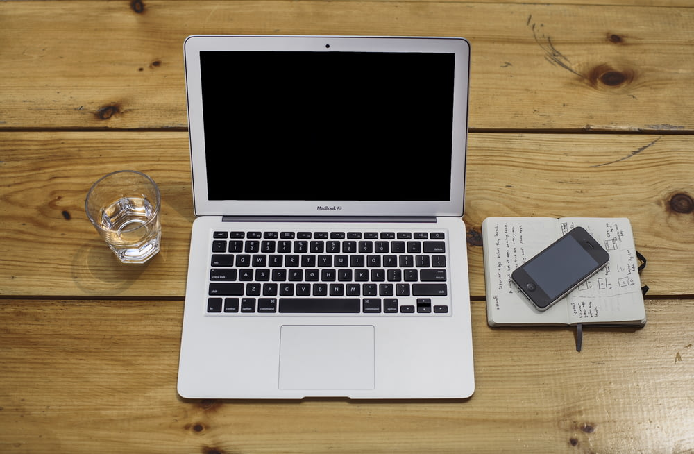MacBook Air beside black iPhone 4 and drinking glass