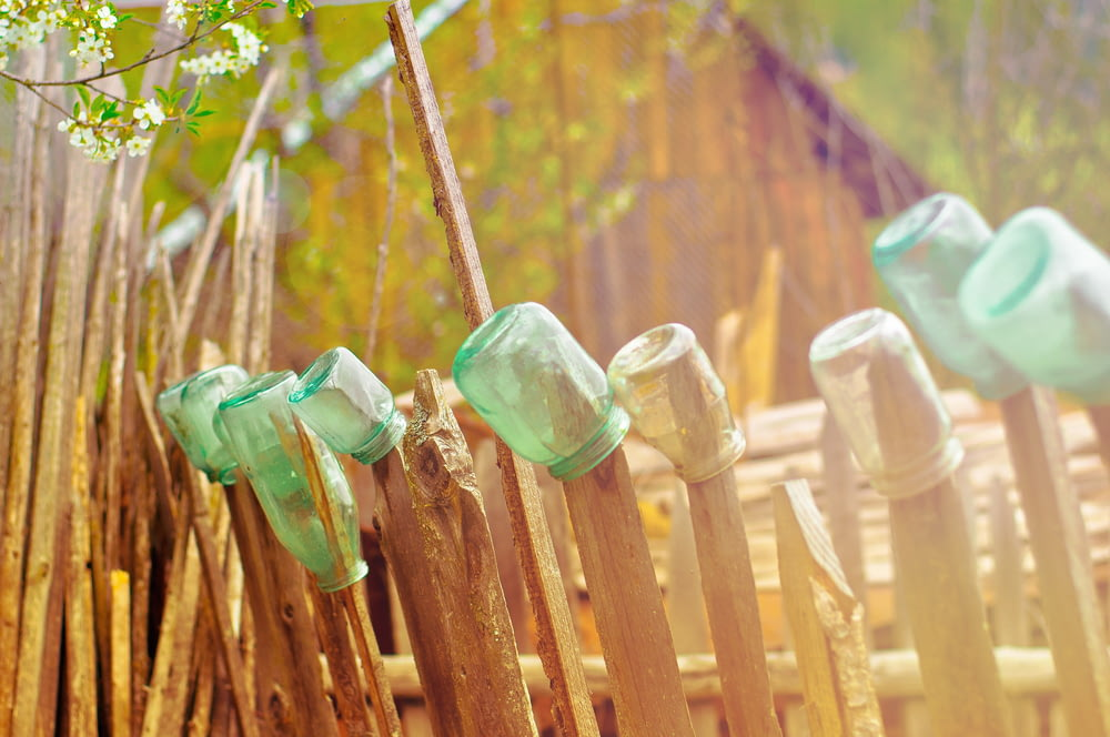 green glass jars on brown wooden fence