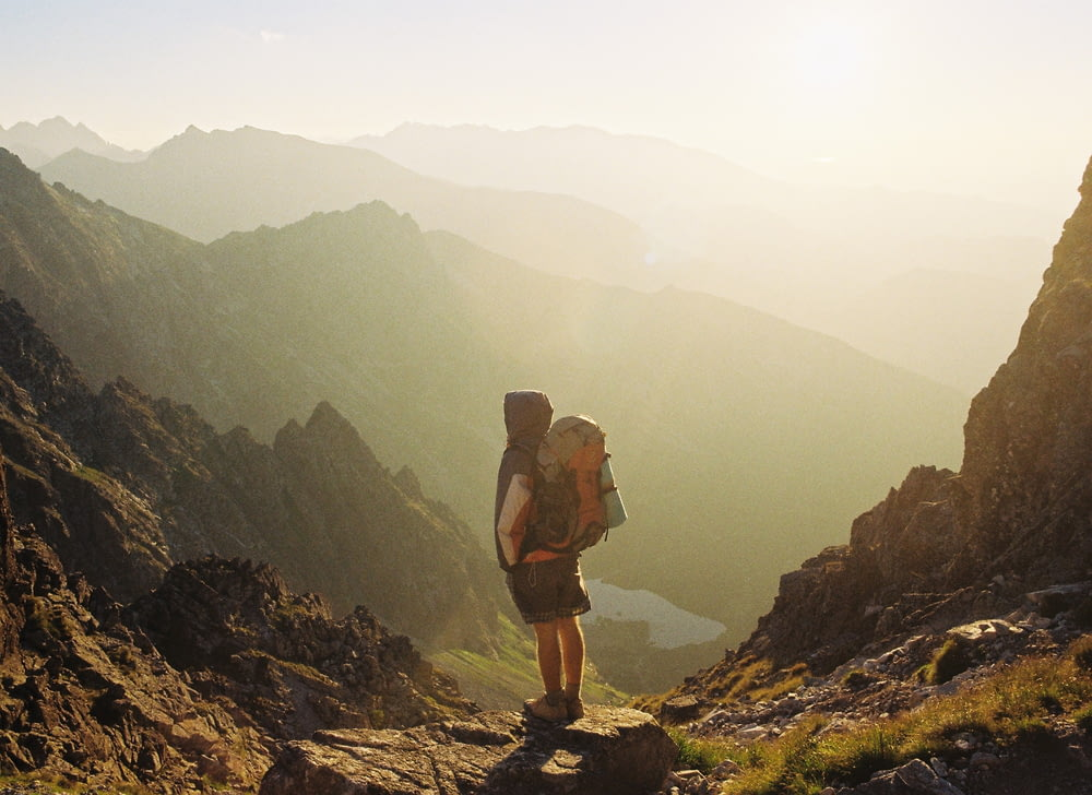 climber standing on rock near overlooking view of mountain at daytime