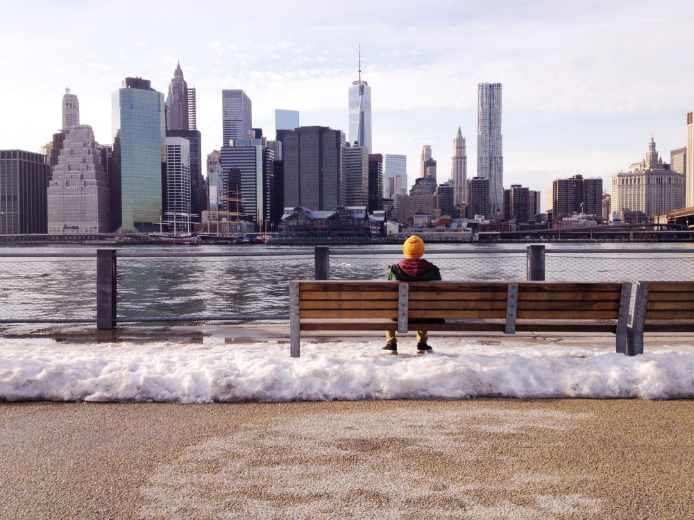 person in knit cap sitting on wooden bench in front of body of water during daytime