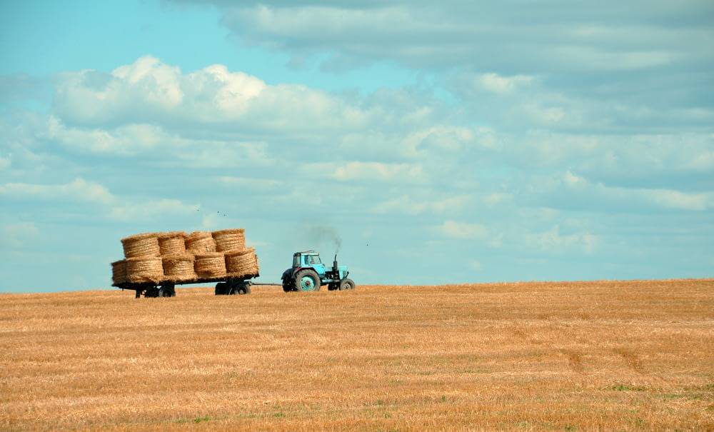 brown hay on tractor under white and blue sky during daytime