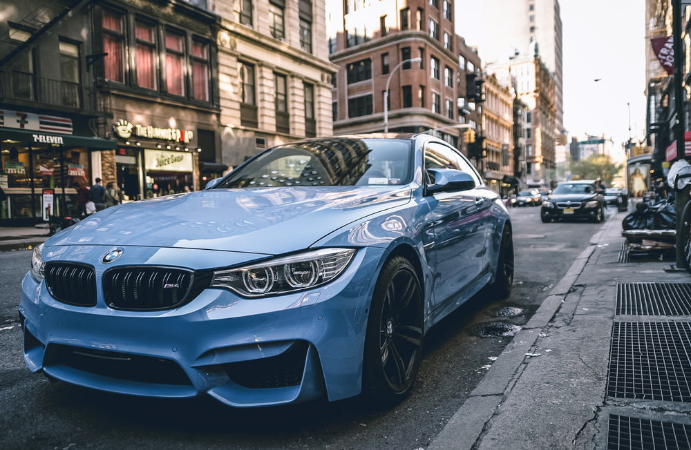 blue BMW coupe parked on the road during daytime