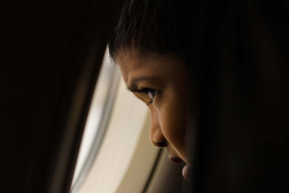 shallow focus photo of boy looking at window