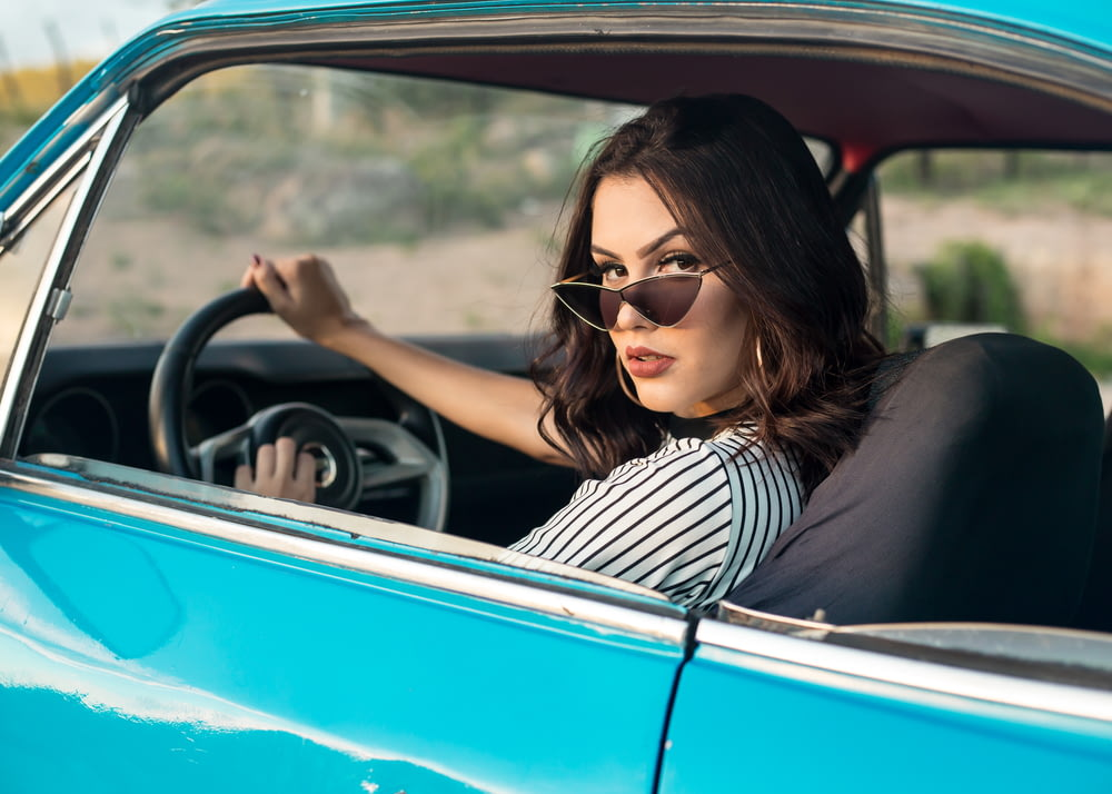 selective focus photography of woman driving blue car