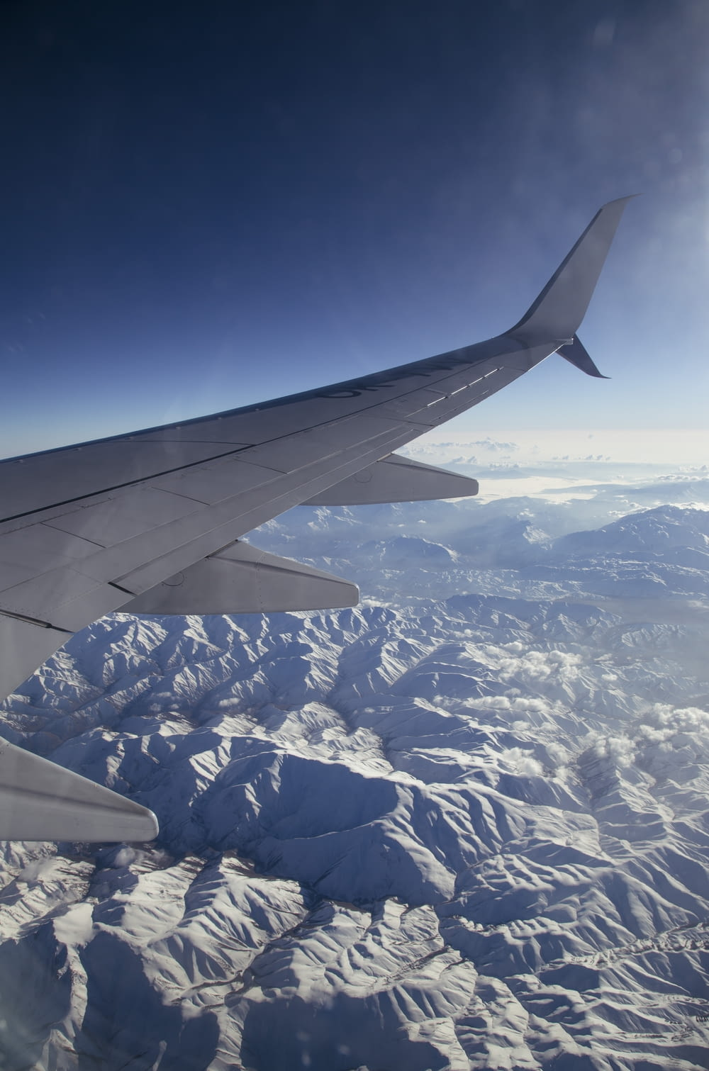 white and black airplane wing over white and blue mountains during daytime