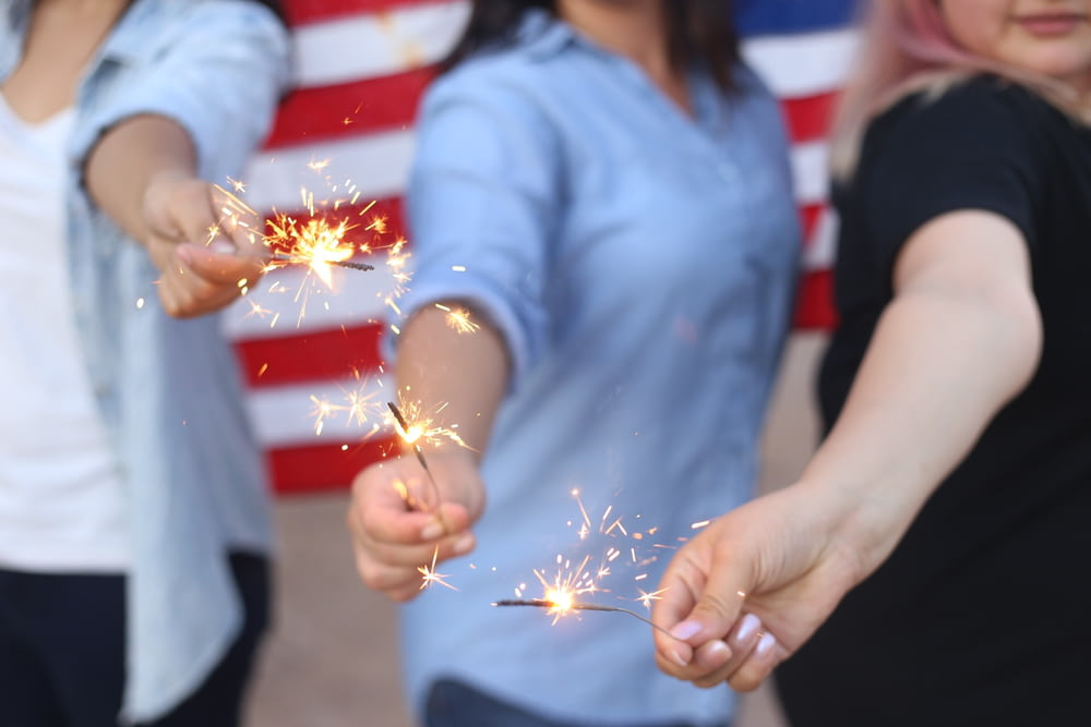 three person holding sparklers