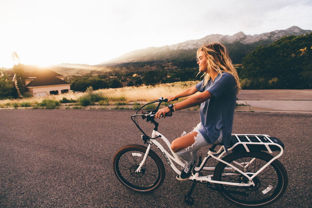 woman in blue t-shirt and distressed blue denim jeans riding white bicycle on grey road near mountains at daytime