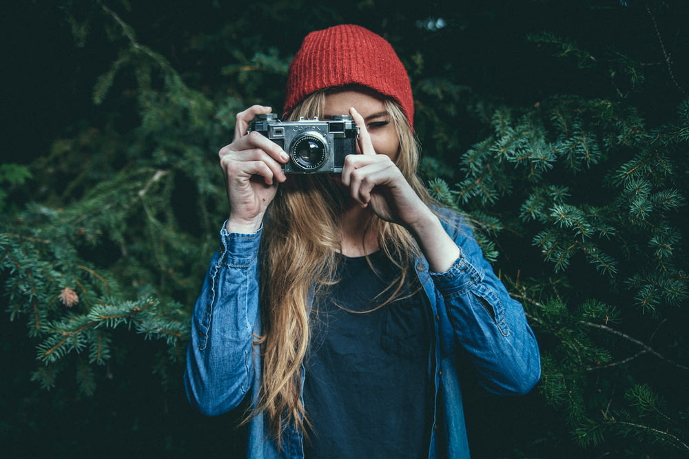 woman standing behind green leaf tree holding DSLR camera