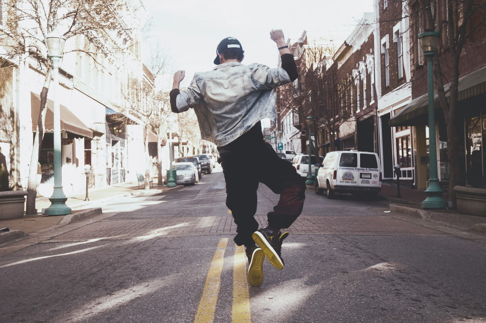 man jumping on the middle of the street during daytime