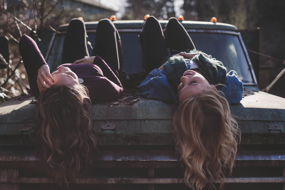 two women lying down on vehicle