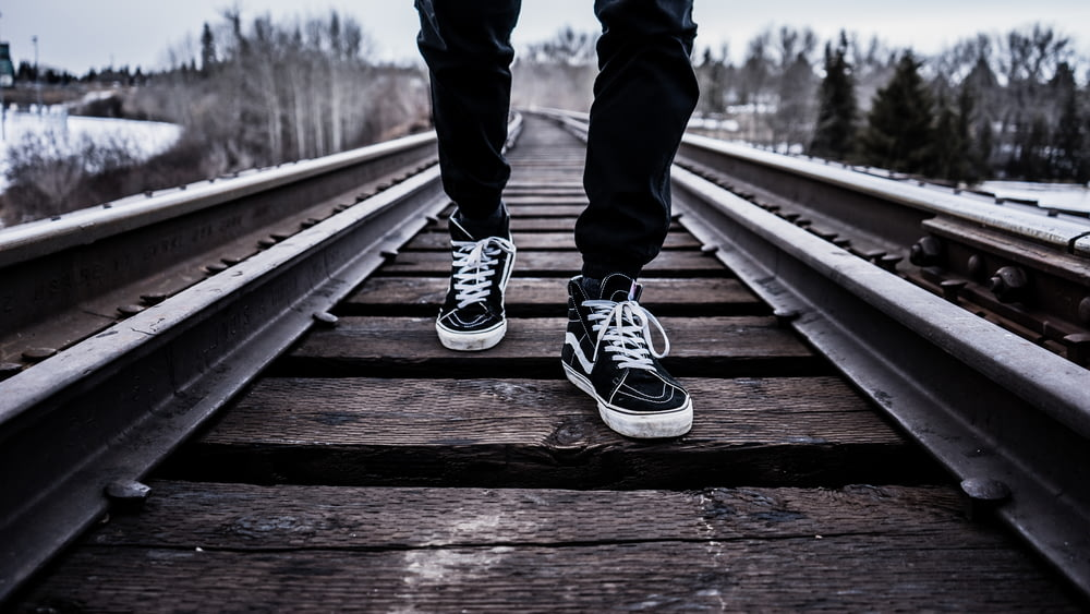 person wearing pair of black-and-white Vans Old Skool shoes walking on brown train tracks during winter