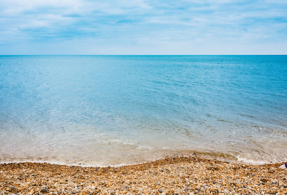 blue body of water under blue sky photography