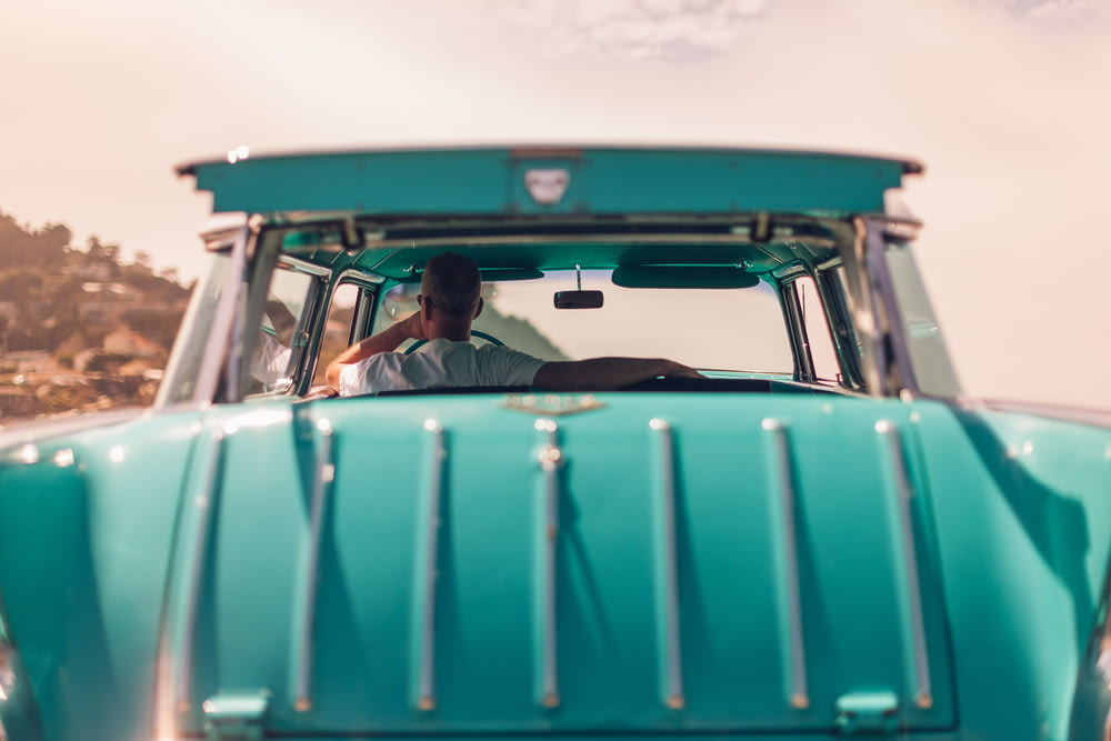 selective focus photography of person riding teal car