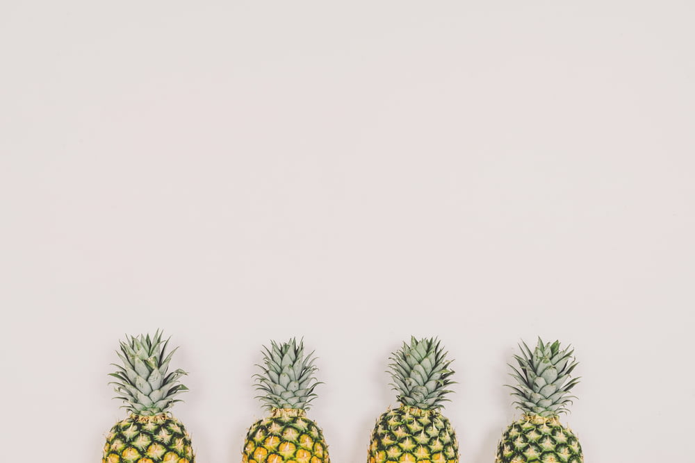 four pineapples on white background