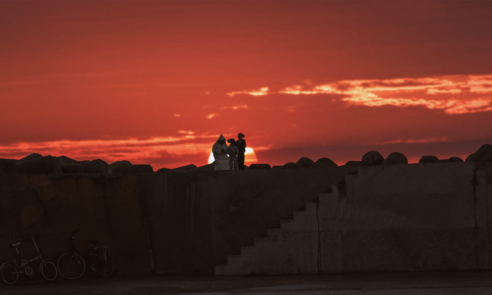 silhouette of man and woman sitting on concrete wall during sunset