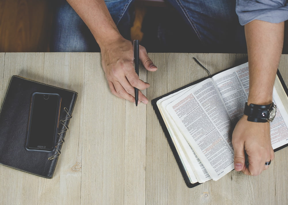 person holding bible with pen