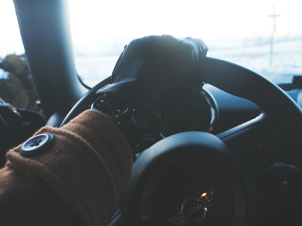 person holding black steering wheel