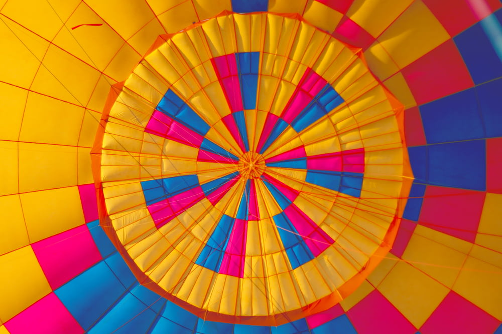 low angle photography of yellow, pink, and black hot air balloon