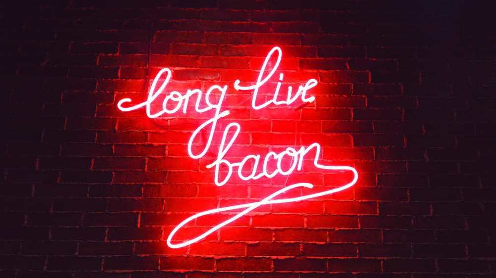 red ling live bacon neon light signage on brown wall bricks