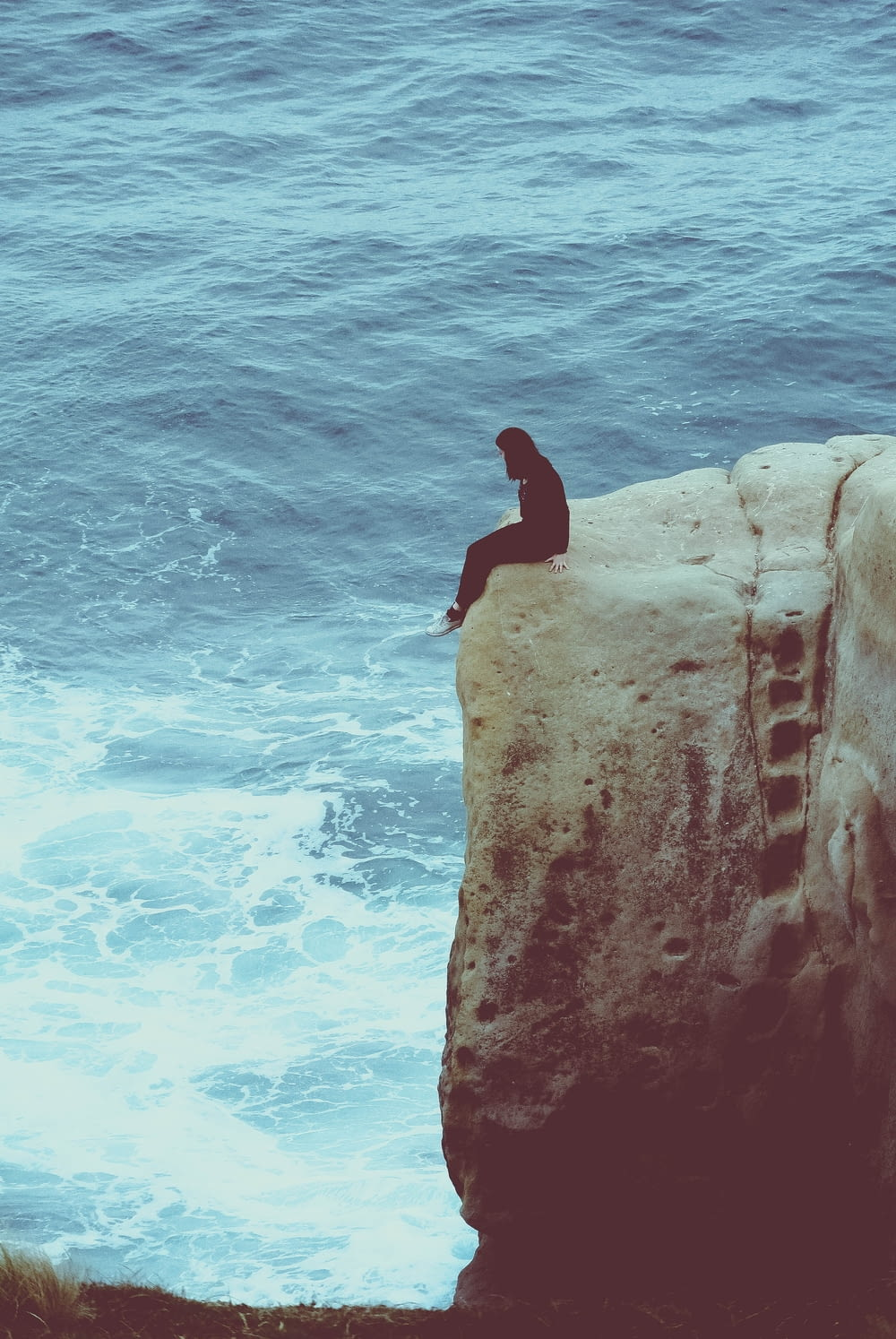 person sitting on edge of rock looking at sea