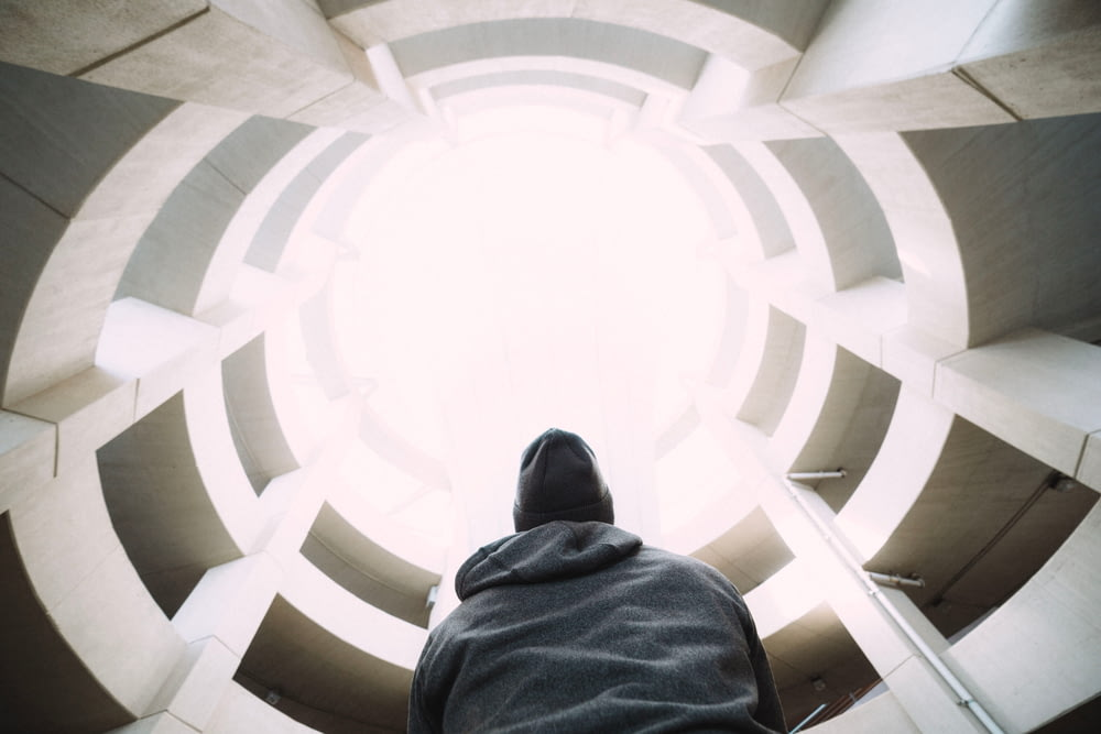 photography of person wearing gray hooded jacket inside building during daytime
