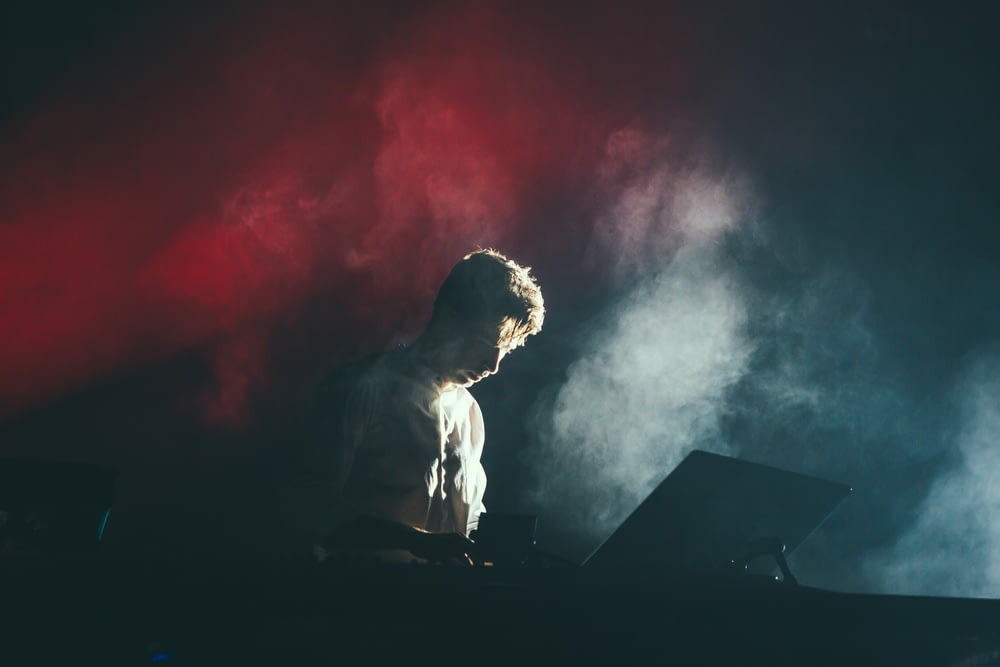 A musician in a white shirt on stage with white and red lights breaking through the smoke behind his back