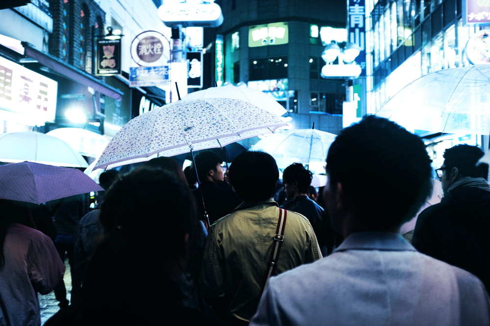 people with umbrellas walking on road in middle of buildings at night