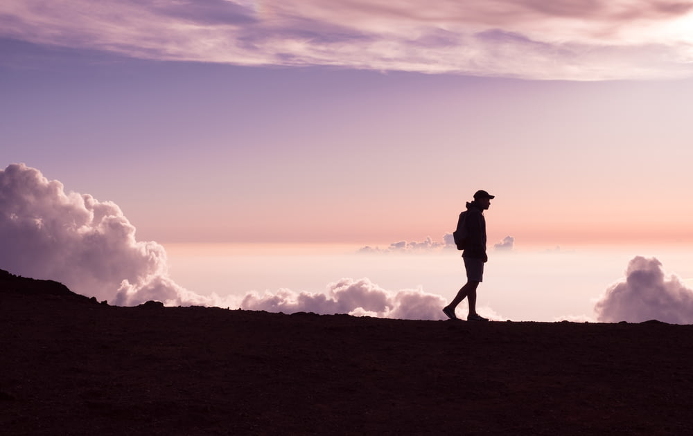 silhouette of person walking under white clouds