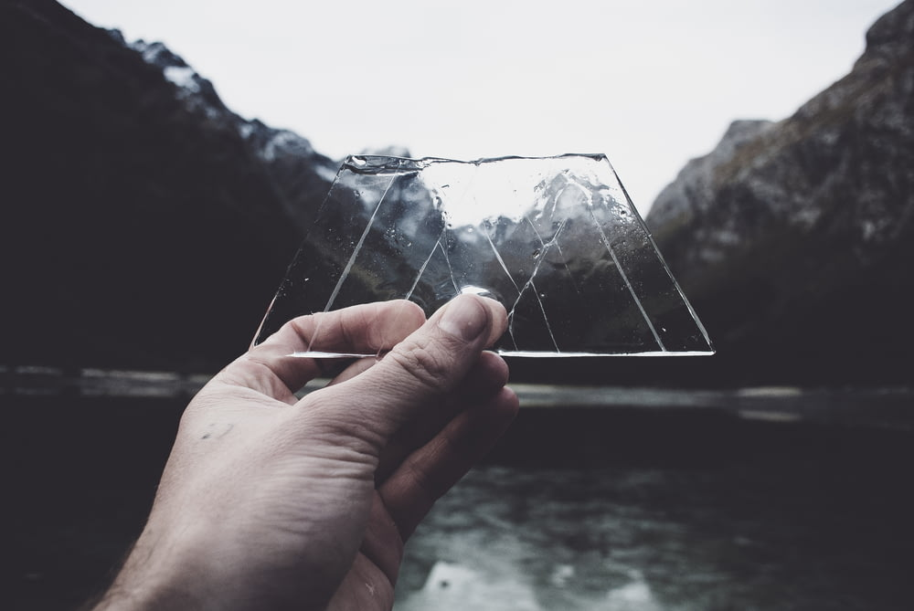 person holding clear glass panel