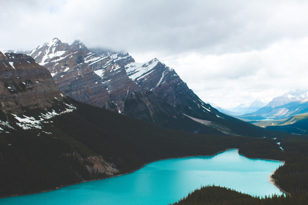 body of water by mountains during daytime