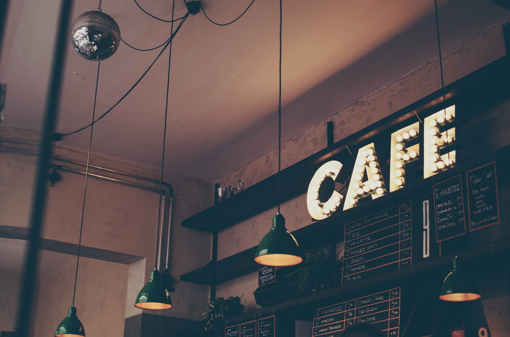 photography of cafe with LED signage and pendant lamps and menu boards