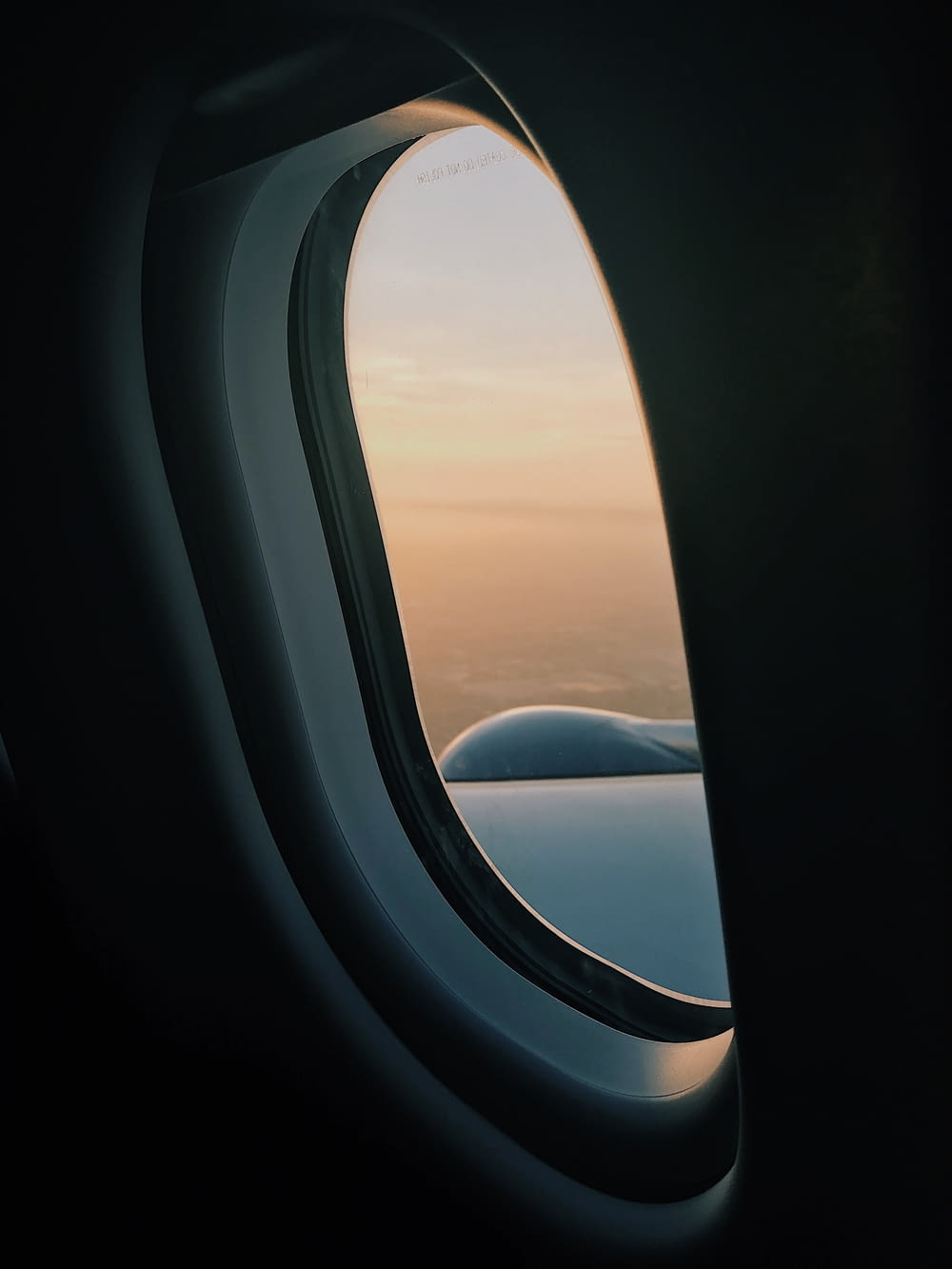 person inside plane at high altitude taking picture of left wing during daytime