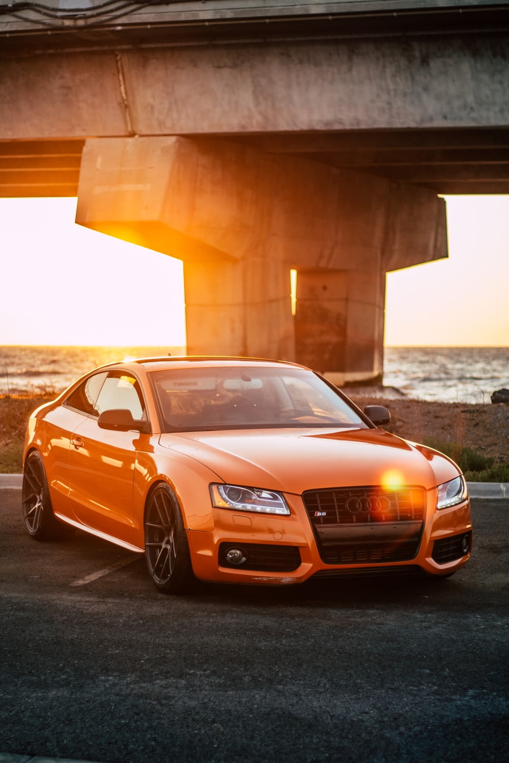orange Audi coupe parked on gray concrete road