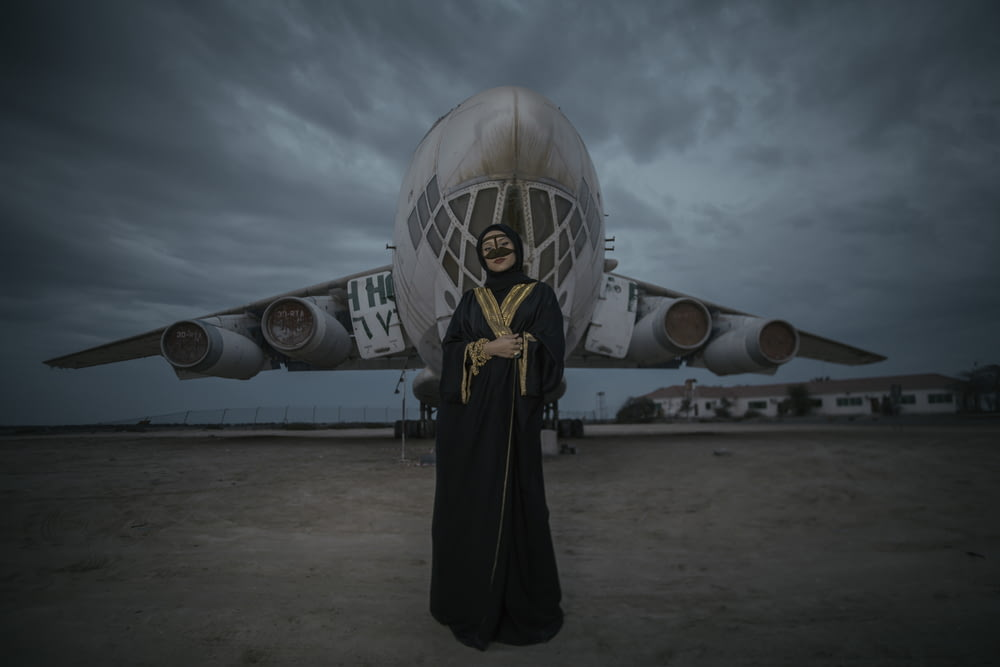 woman wearing black dress standing near white plane