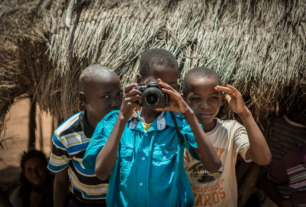 two boys standing behind boy using camera