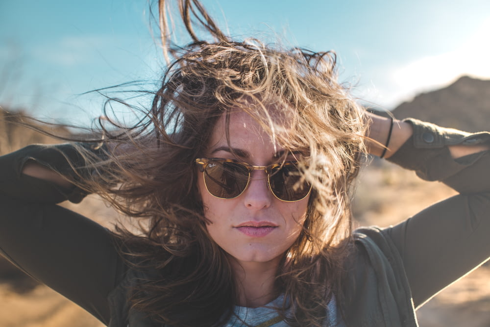 closeup photo of woman holding her hair