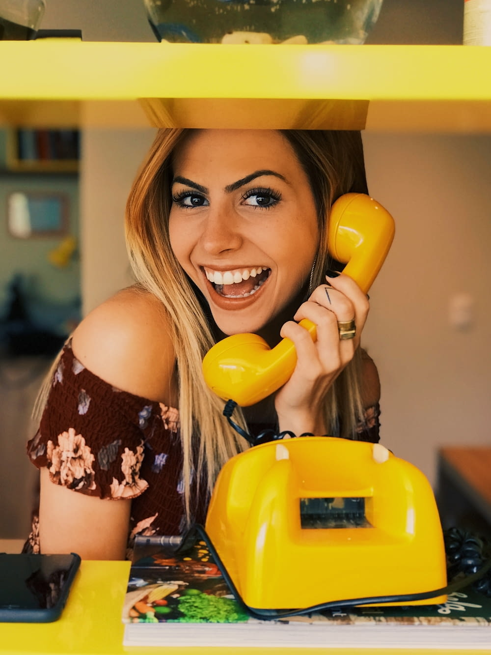 woman holding yellow rotary telephone