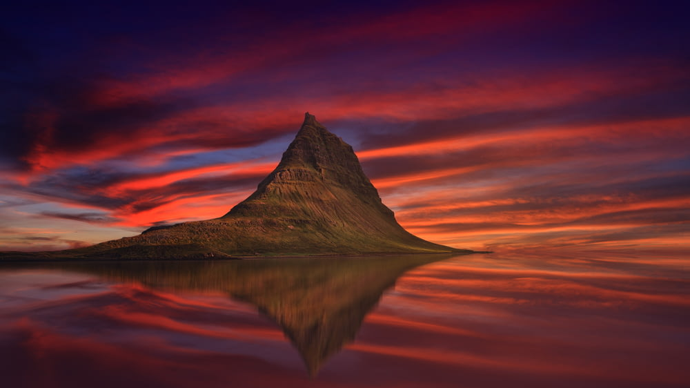 in distant photo of brown butte rock in front of calm body of water under orange clouds