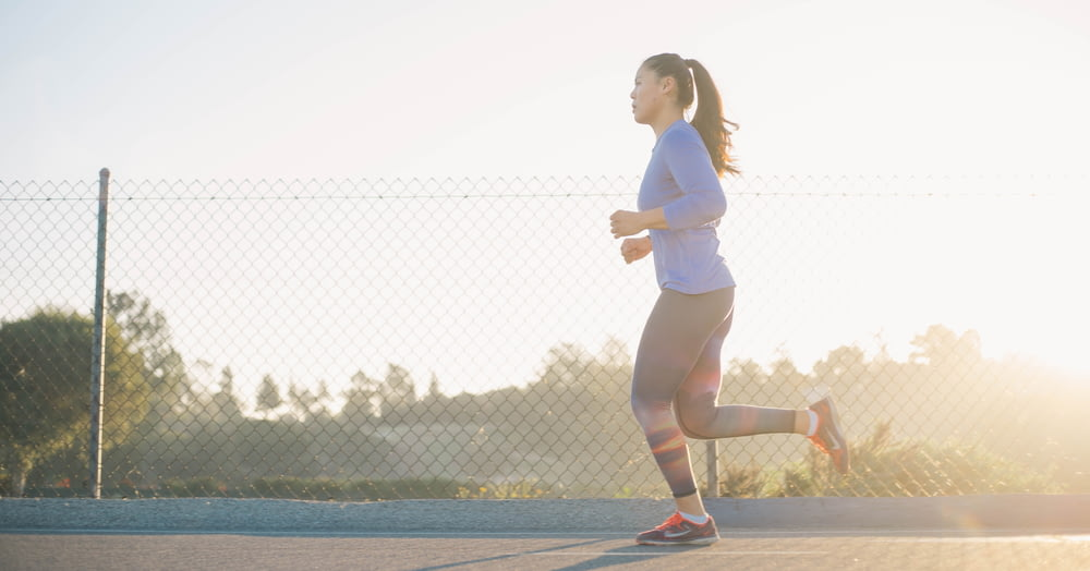 woman jogging near wire fence