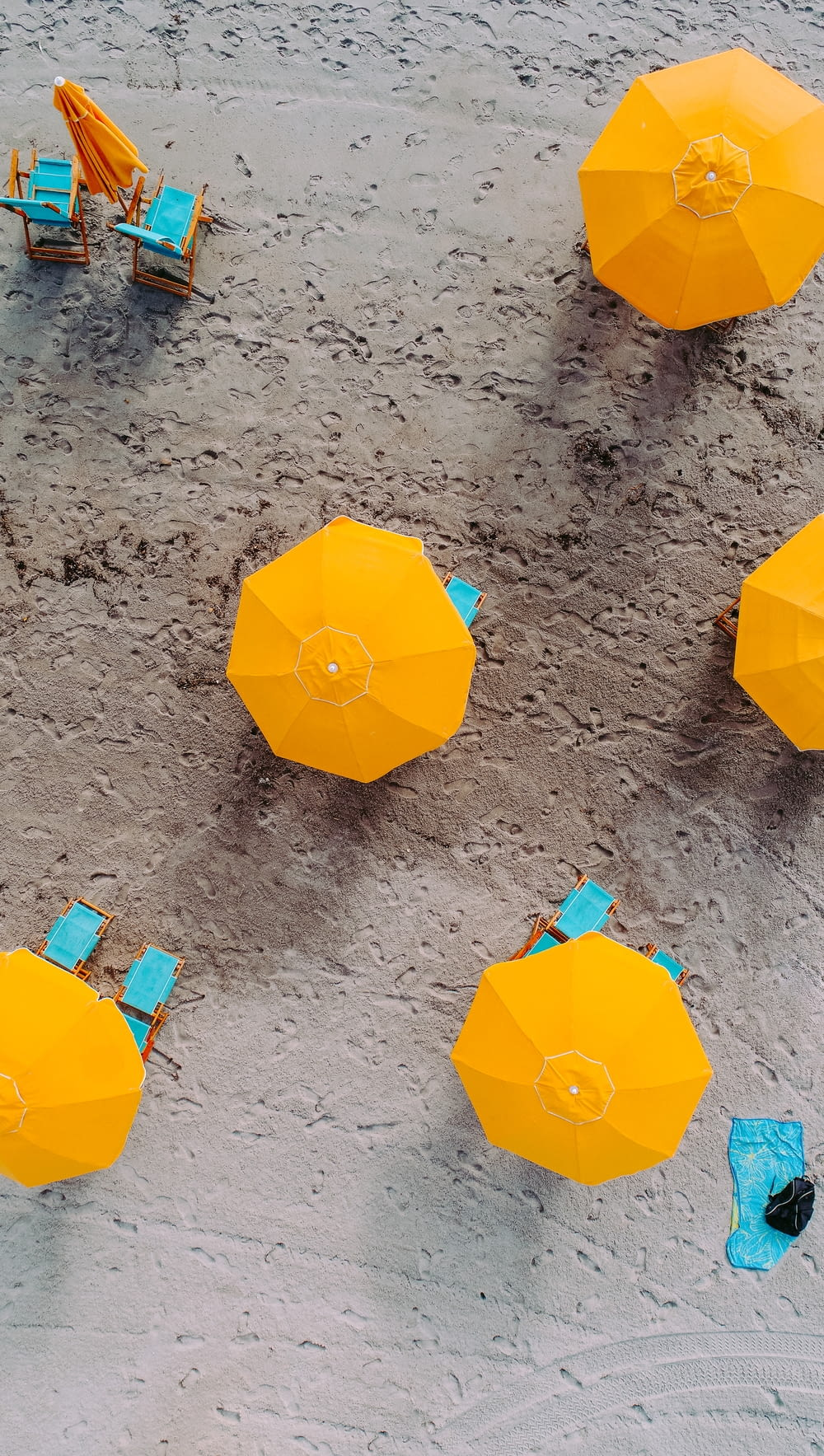 five yellow umbrellas on sand at daytime