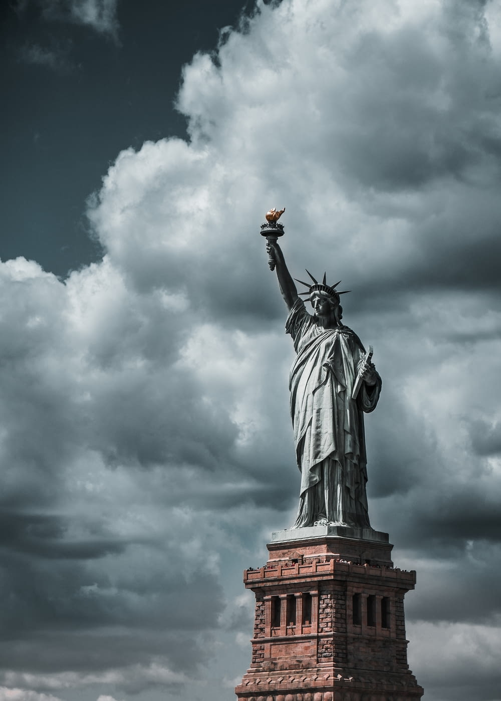 Statue of Liberty under cloudy sky during daytime