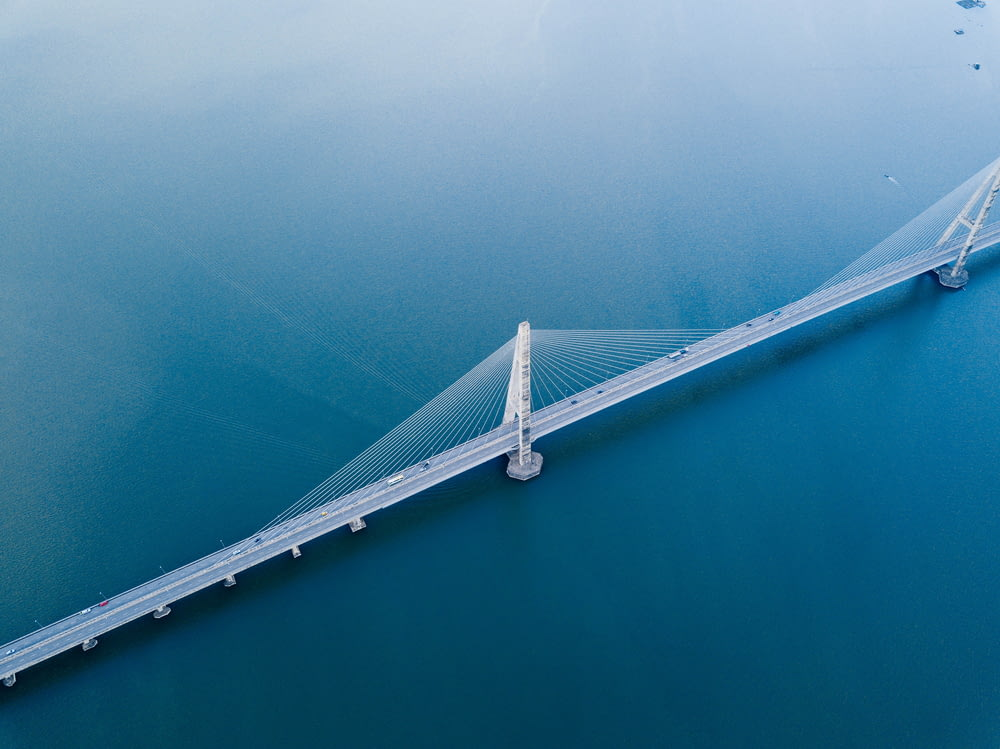 gray concrete bridge on body of water in aerial photography
