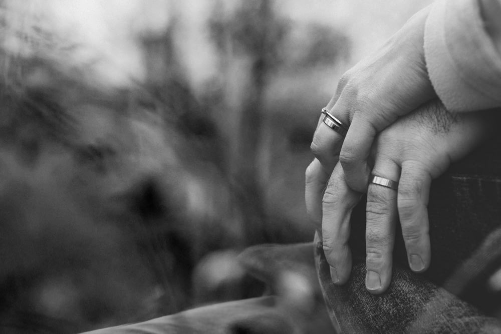 grayscale photo of two person holding hands with wedding rings