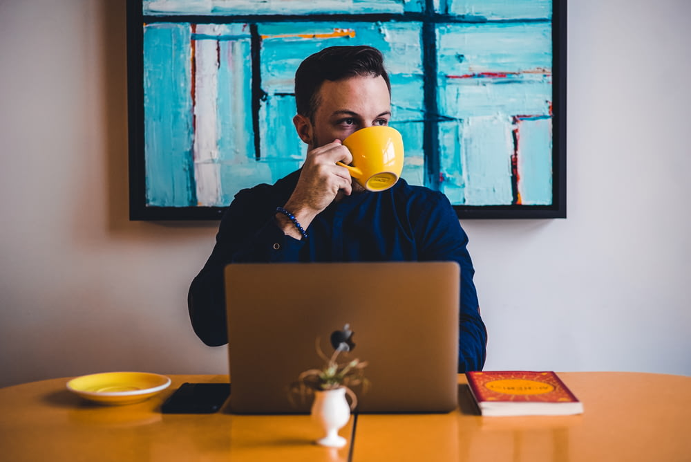 man drinking coffee in front of the laptop computer