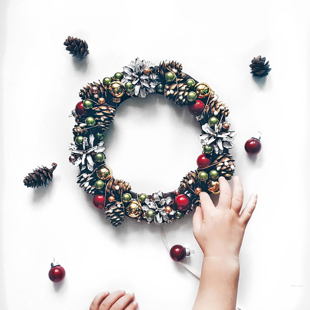person making bauble and pinecone wreath