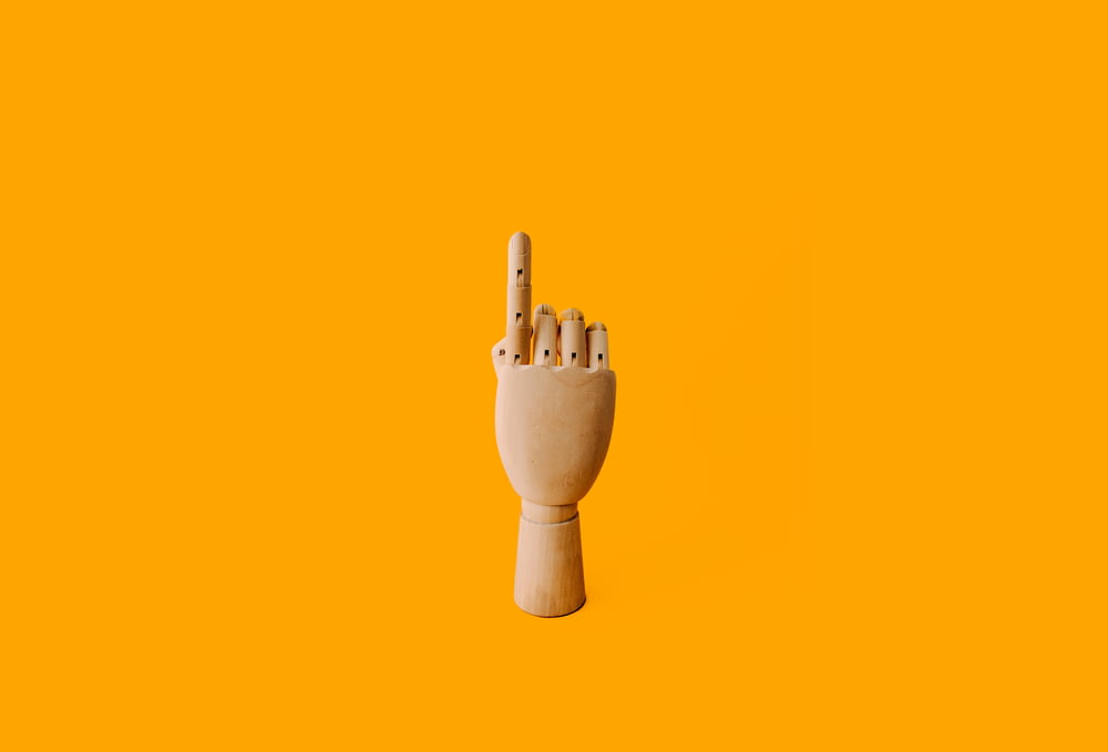 beige wooden hand sculpture with orange background