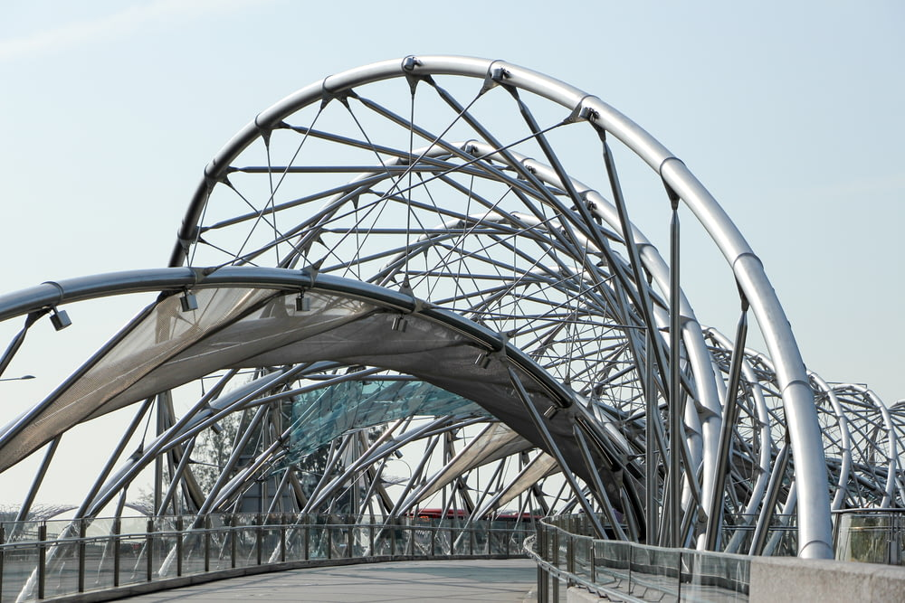 low angle photography of pathway under gray metal spiral frame