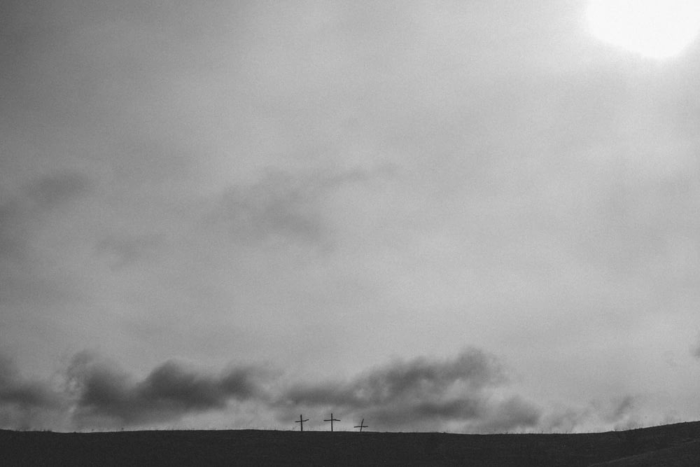 three cross under cloudy sky
