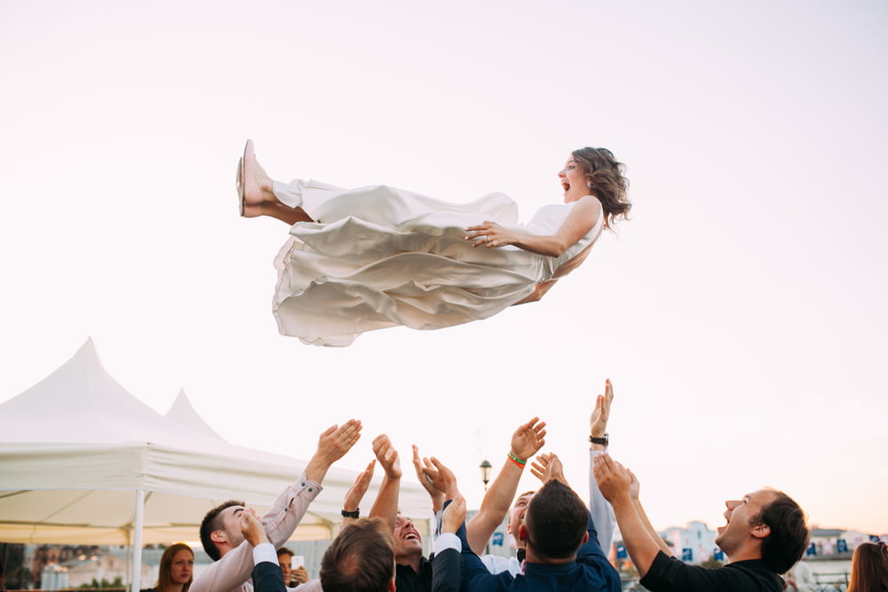 people lifting woman in the air