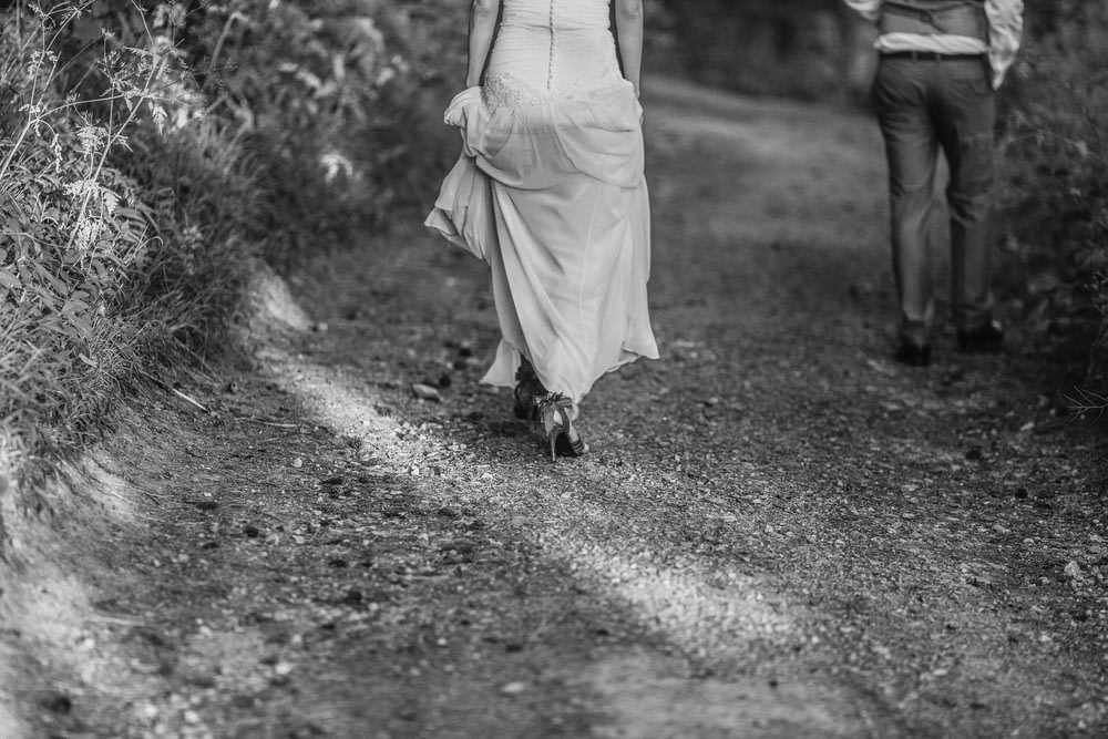 grayscale photography of man and woman walking on pathway